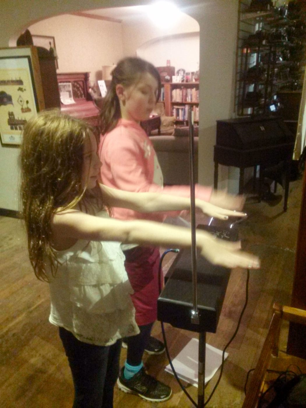 Girls try out a Theramin at the SPARK Museum, Bellingham, WA