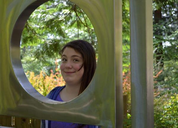 Girl peering through metal sculpture